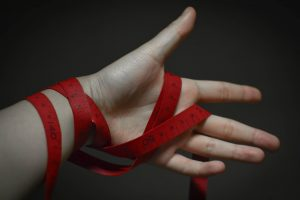 A red tape or ribbon around a hand